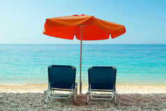 Blue sunbeds and orange umbrella (parasol) on Paradise Beach in Stock Photo