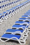 Blue sunbeds on pebble beach Royalty Free Stock Photography