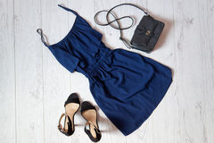 Blue sundress, a black handbag and shoes on a wooden background. Fashionable concept Royalty Free Stock Photos