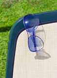 Blue sunglasses on a chaise lounge. And green grass royalty free stock photos