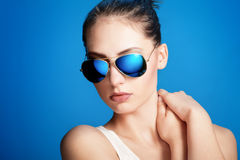 Blue sunglasses. Close-up portrait of beautiful young girl in blue sunglasses on dark blue background Royalty Free Stock Photography