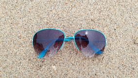 Blue Sunglasses in the sand stock images