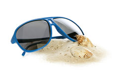 Blue sunglasses, sand and shells Stock Photography