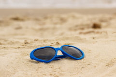 Blue sunglasses shaped heart on the sand Stock Photography