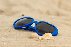 Blue sunglasses shaped heart with shells on the sand Stock Images