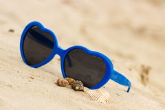 Blue sunglasses shaped heart with shells on the sand Stock Photos