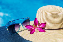 Blue sunglasses and straw hat with orchid flower near swimming p Stock Image