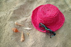 Blue sunglasses and vivid pink straw hat on the sand beach with little seashells. Blue sunglasses and vivid pink straw hat on the sand beach with many types of Stock Images