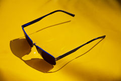 Blue Sunglasses on a yellow Sunbed. Casting a deep shaddow Royalty Free Stock Photos