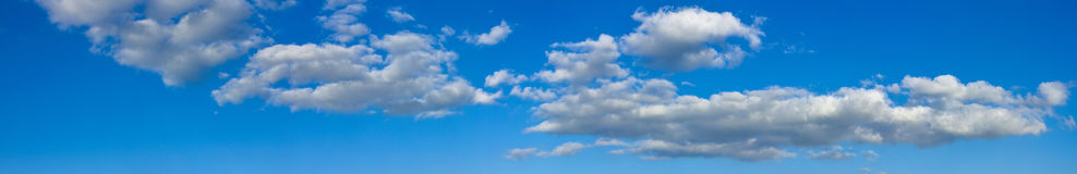 Blue sunny sky with white clouds landscape banner. Huge panorama Stock Images