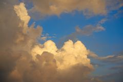 Blue sunset sky golden cumulus clouds. Background Stock Photo