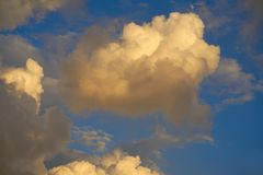 Blue sunset sky golden cumulus clouds. Background Stock Photography