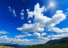 Blue sunshiny sky with white clouds over mountain. Royalty Free Stock Photos