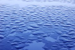 Blue surface covered with water drops Royalty Free Stock Images
