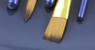 Brushes for drawing. On the blue surface are paint brushes stock video footage