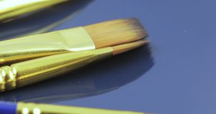 Brushes for drawing. On the blue surface are paint brushes stock footage