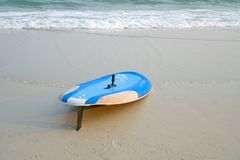A blue surfboard on the beach royalty free illustration