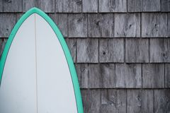 Blue surfboard and cedar shingles. A blue and white surfboard leans up against a grey shingled wall Royalty Free Stock Photo