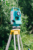 Blue surveying equipment total station on a background of lake and forest Royalty Free Stock Images