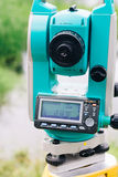 Blue surveying equipment total station on a background of lake and forest Stock Image