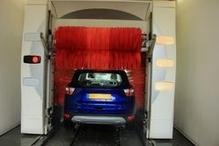 Automatic car wash. A blue SUV in an automatic car wash with big red brushes royalty free stock image