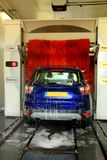 Automatic car wash. A blue SUV in an automatic car wash. Text on machine: program items in Dutch royalty free stock photos