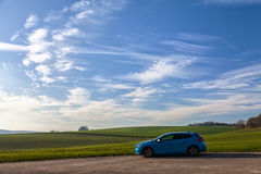 Blue Suv Near Green Plains Under White Cloudy Sky during Daytime Royalty Free Stock Photo