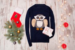 Blue sweater with an owl on a wooden background. Fur-tree branch with Christmas decorations Stock Photos