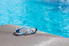 Blue swimming goggle isolated on brown fabric chair with copy sp. Blue swimming goggles isolated on brown fabric chair and clear blue water background with copy royalty free stock image