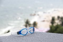 Blue swimming goggle isolated with sea and beach background with. Blue swimming goggles isolated with blurred sea sand and beach on vacation summer background royalty free stock photos
