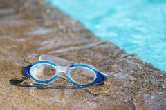 Blue swimming goggle isolated on swimming pool edges with copy s. Blue swimming goggles isolated on swimming pool edges and clear blue water background with copy royalty free stock photo