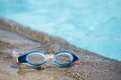 Blue swimming goggle isolated on swimming pool edges with copy s. Blue swimming goggles isolated on swimming pool edges and clear blue water background with copy stock photo