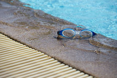 Blue swimming goggle isolated on swimming pool edges with copy s. Blue swimming goggles isolated on swimming pool edges and clear blue water background with copy stock images