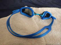Blue swimming googles with a towel. A blue swimming googles with a towel Stock Photography