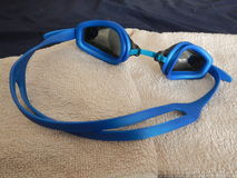 Blue swimming googles with a towel. A blue swimming googles with a towel Royalty Free Stock Image