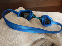 Blue swimming googles with a towel. A blue swimming googles with a towel Royalty Free Stock Images