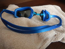 Blue swimming googles with a towel. A blue swimming googles with a towel Stock Photos