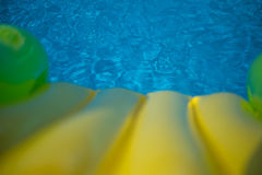 Blue swimming pool with children's slide, background. Blue swimming pool with yellow green children's slide Stock Photos