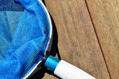 Pool cleaning net on wooden decking royalty free stock photography