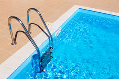 Blue swimming pool with ladder Stock Photos
