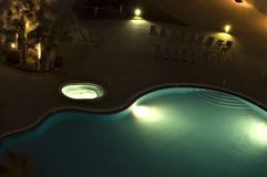 Blue Swimming Pool with Lights. Partial view of blue swimming pool and hot tub at night with lights, palm trees and lounge chairs Stock Photos
