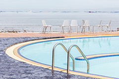 Blue swimming pool with relaxing beach chairs in background. Stock Photography