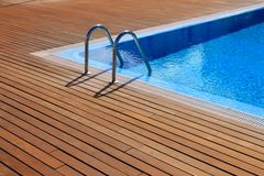 Blue swimming pool with teak wood flooring Royalty Free Stock Images
