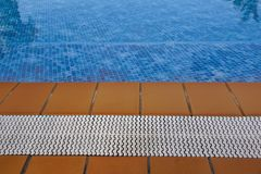 Blue swimming pool with teak wood flooring stripes summer vacation.  Royalty Free Stock Images