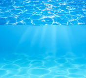 Blue swimming pool water surface and underwater. Blue pool water surface and underwater with sun sparkles and beams stock photo