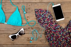 Blue swimsuit, dress, sunglasses and smart phone on brown wooden table. Travel concept - summer women& x27;s fashion with blue swimsuit, dress, sunglasses and Stock Images