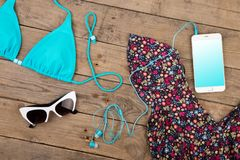 blue swimsuit, dress, sunglasses and smart phone on brown wooden table stock photos