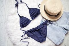 Blue swimsuit, straw hat and denim shorts. White fur on the back. Ground, top view Stock Photo