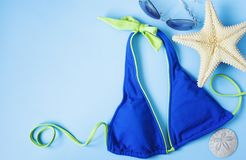 Blue swimsuit, sunglasses and starfish on blue background. Beach background concept stock photo
