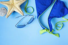 Blue swimsuit, sunglasses and starfish on blue background. Beach background concept royalty free stock image